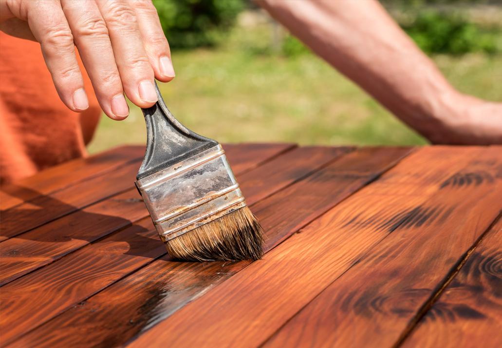 Mann streicht Holz mit Leinöl