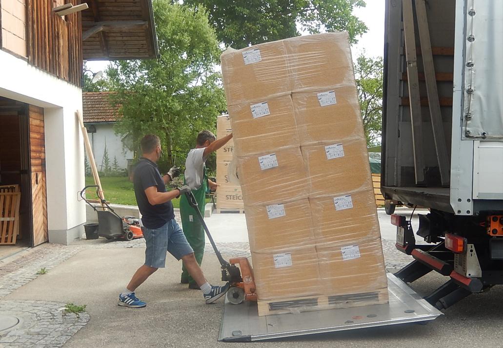 Dämmplatten werden von einem LKW mit Hebebühne abgeladen